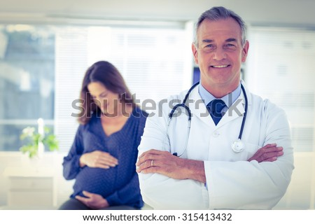 Portrait of confident male doctor with pregnant woman in background at clinic - stock photo