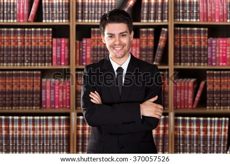 Portrait of confident male lawyer standing arms crossed against bookshelf in office
