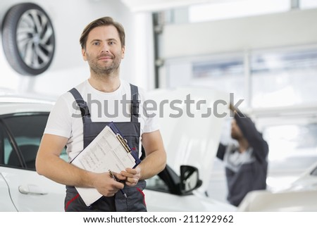 Portrait of confident male maintenance engineer with clipboard in car repair shop - stock photo