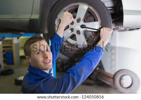 Portrait of confident male mechanic changing car tire - stock photo