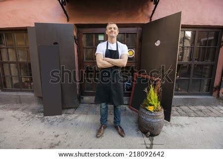 Portrait of confident male salesperson standing arms crossed outside coffee store - stock photo