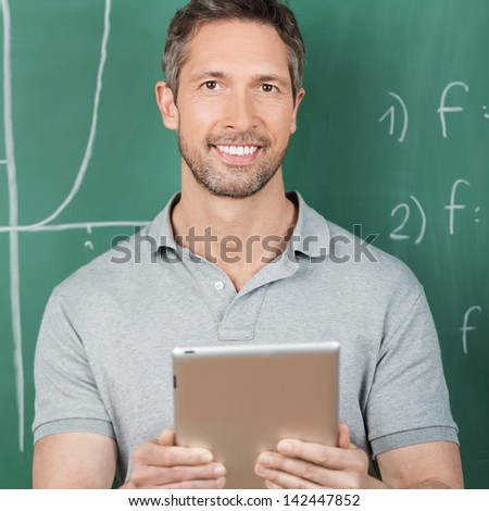 Portrait of confident male teacher holding digital tablet against chalkboard in classroom - stock photo