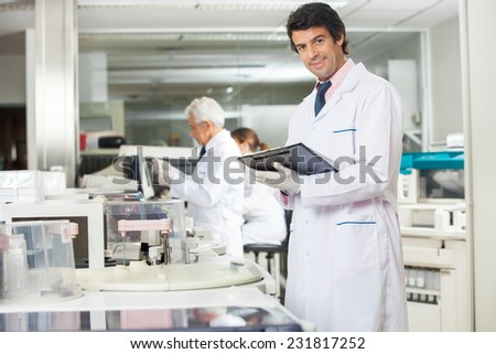 Portrait of confident male technician with clipboard in laboratory