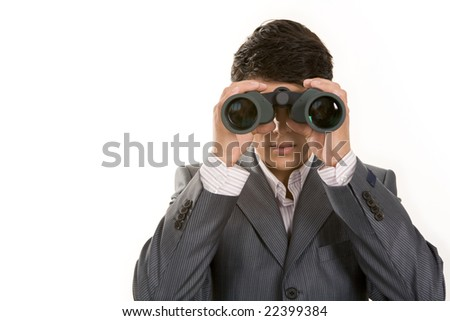 Portrait of confident man in suit observing through binoculars - stock photo