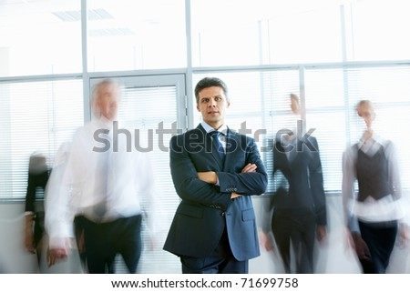 Portrait of confident man looking at camera in office with busy people passing by behind - stock photo