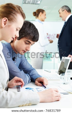 Portrait of confident man looking at document with female near by in working environment