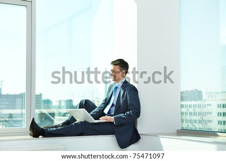 Portrait of confident man sitting with laptop in office - stock photo