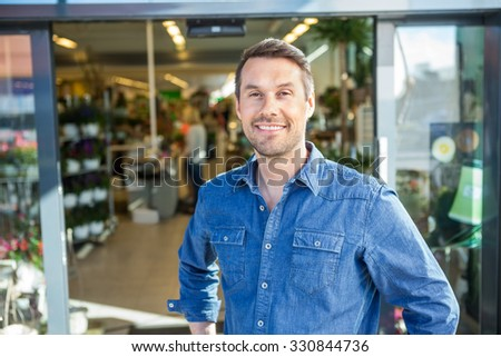 Portrait of confident man standing outside flower shop - stock photo