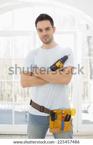 Portrait of confident man with hand drill in new house - stock photo
