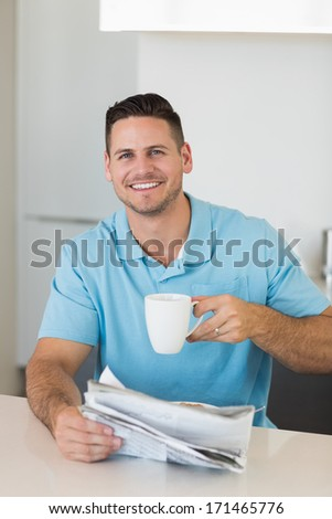 Portrait of confident man with newspaper holding coffee cup at table in house - stock photo