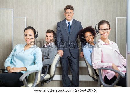 Portrait of confident manager with customer service representatives in office - stock photo