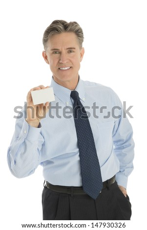 Portrait of confident mature businessman showing blank business card against white background - stock photo