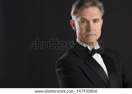 Portrait of confident mature man in tuxedo staring against black background - stock photo