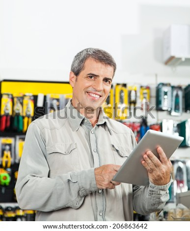 Portrait of confident mature man using tablet computer in hardware store - stock photo