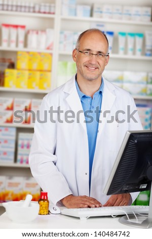 Portrait of confident mature pharmacist standing at counter in pharmacy - stock photo