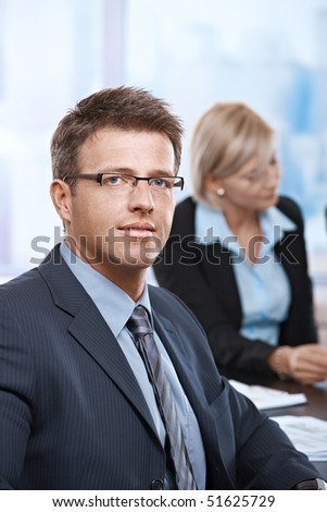 Portrait of confident mid-adult businessman looking at camera office.
