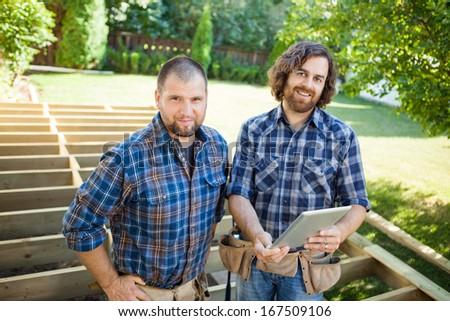 Portrait of confident mid adult construction workers with digital tablet at construction site - stock photo