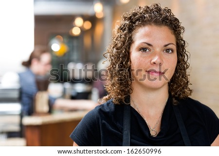 Portrait of confident mid adult female owner at cafe - stock photo
