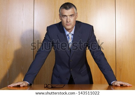 Portrait of confident middle aged businessman leaning at wooden table - stock photo