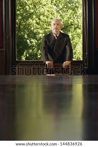 Portrait of confident middle aged businessman standing at conference table - stock photo