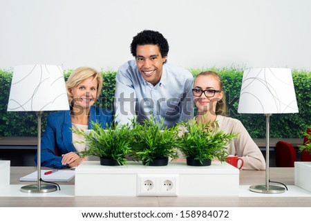 Portrait of confident multiethnic environmentalists at desk in office - stock photo
