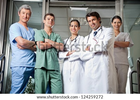 Portrait of confident multiethnic medical professionals standing together with hands folded