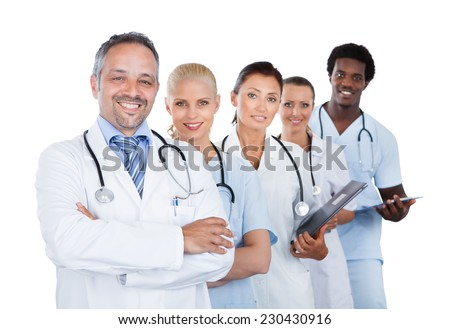 Portrait of confident multiethnic medical team standing in row over white background - stock photo