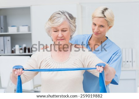 Portrait of confident nurse assisting senior woman in exercising with resistance band in clinic - stock photo