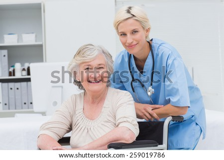 Portrait of confident nurse leaning on senior patients wheelchair at clinic - stock photo