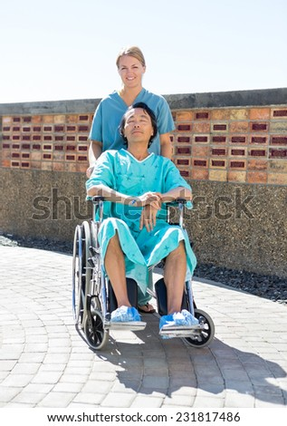 Portrait of confident nurse pushing relaxed patient on wheelchair at courtyard - stock photo
