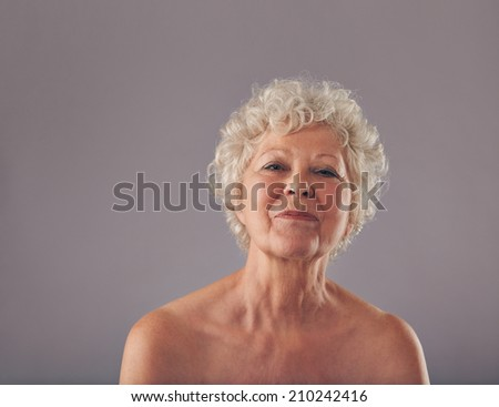 Portrait of confident old woman against grey background. Naked head and shoulders of senior female. - stock photo