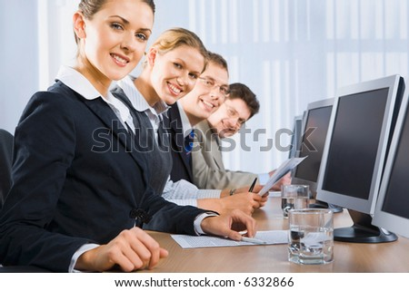 Portrait of confident people sitting in a line in front of monitors and looking at camera - stock photo