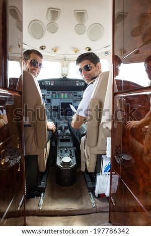 Portrait of confident pilot and copilot in cockpit of private jet - stock photo