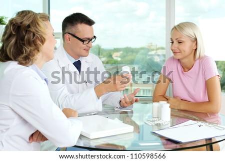 Portrait of confident practitioner describing new vitamins to patient in hospital - stock photo