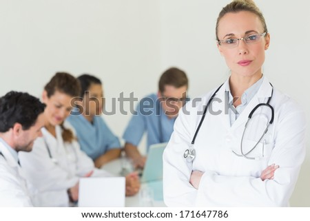 Portrait of confident professional doctor with colleagues in background at hospital