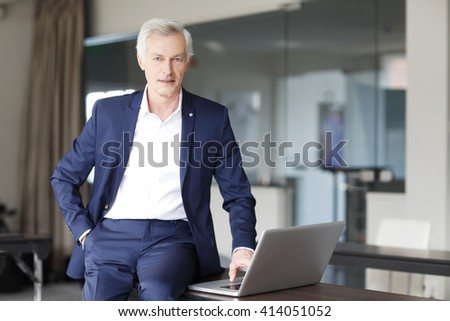 Portrait of confident professional man using laptop while working at his workplace. - stock photo