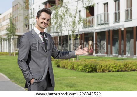 Portrait of confident real estate agent presenting office building - stock photo