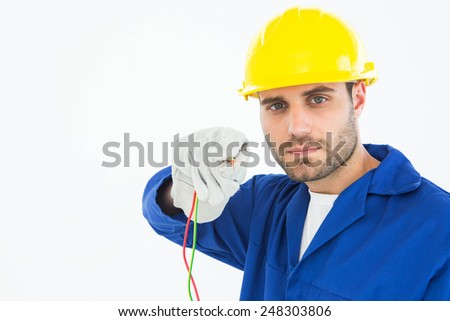 Portrait of confident repairman holding cables against white background