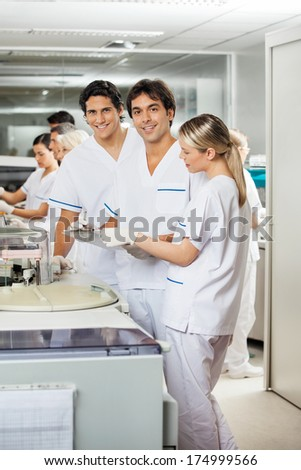 Portrait of confident researchers with colleagues in laboratory - stock photo