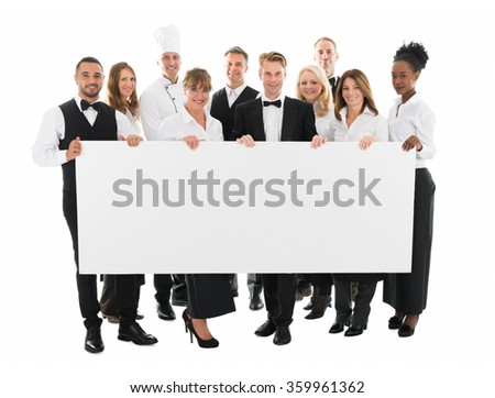 Portrait of confident restaurant staff holding blank billboard against white background - stock photo