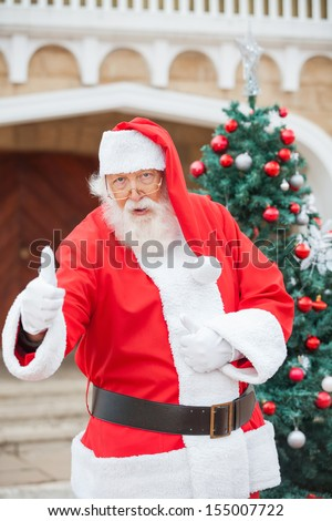 Portrait of confident Santa Claus gesturing thumbsup against Christmas tree - stock photo
