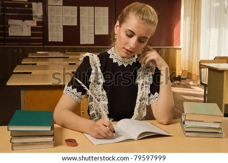 Portrait of confident school girl at her desk - stock photo