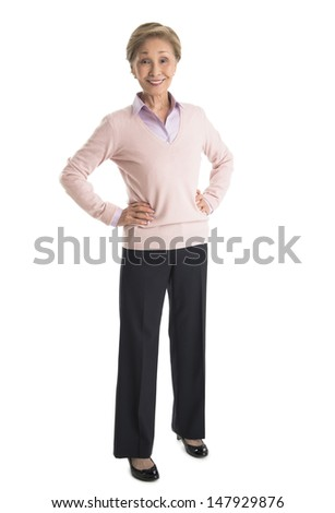 Portrait of confident senior businesswoman standing with hands on hips isolated over white background - stock photo