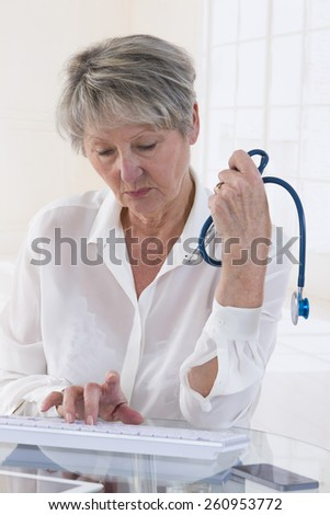 Portrait of confident senior female doctor using computer in clinic or hospital - stock photo