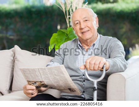 Portrait of confident senior man with newspaper and walking stick sitting on couch at nursing home porch - stock photo