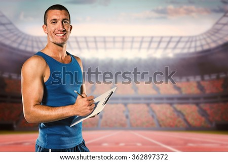 Portrait of confident sports coach writing on clipboard against race track - stock photo
