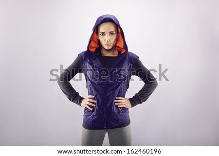 Portrait of confident sportswoman standing with her hands on hips against grey background with copyspace. Female athlete in sports wear looking at camera - stock photo