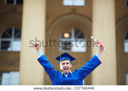 Portrait of confident student with graduation certificate showing gladness - stock photo