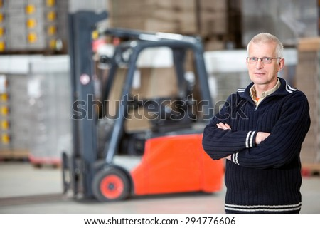 Portrait of confident supervisor with arms crossed standing at distribution warehouse - stock photo