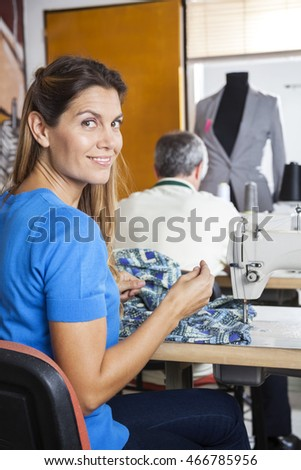 Portrait Of Confident Tailor Sitting At Workbench